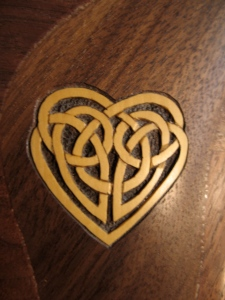 Celtic knotwork heart carved and inlain into a custom Raphael26  Claro Walnut Therapy harp. Made of Boxwood